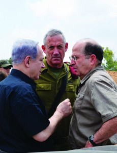 Prime Minister Binyamin Netanyahu (L) conferring with IDF Chief of Staff Benny Gantz (C) and Defense Minister Moshe Yaalon (R) at the Command and Control Center of the 162nd Armor Division in Southern Israel on Monday.  (Kobi Gideon/GPO/Flash90)