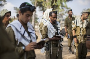 Israeli soldiers daven at a deployment area near the border with the Gaza Strip, on Monday. (Yonatan Sindel/Flash90)