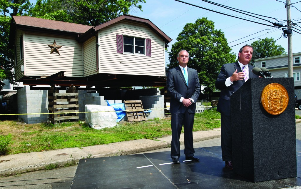 Gov. Chris Christie, with state environmental protection commissioner Robert Martin, (L) on Monday talks about the state's efforts to raise homes above flood level in Keansburg, N.J. (AP Photo/Mel Evans)