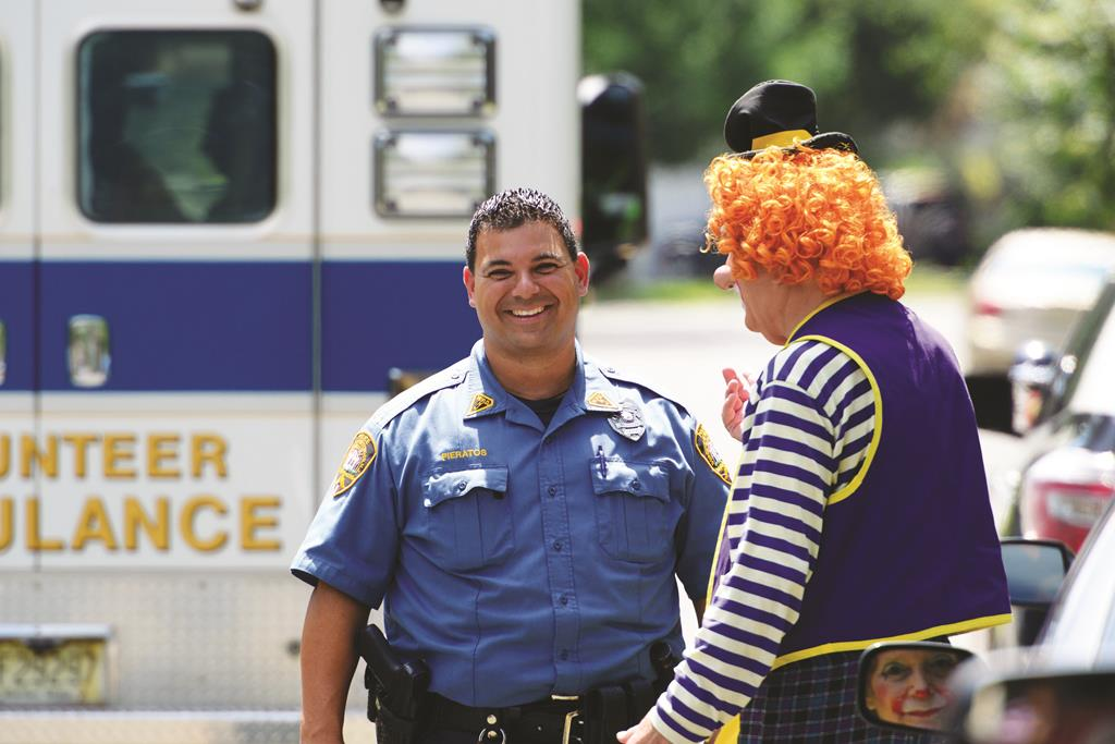 """Westwood Police Officer Niko Pieratos on Monday talks with Jack """"Poppi T Clown"""" Erbstein at the accident site of another clown in Westwood, N.J. (AP Photo/Northjersey.com, Tariq Zahawi)"""