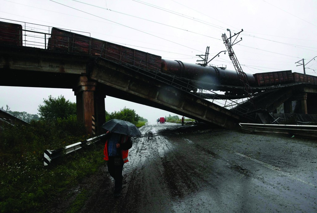 A man holding an umbrella walks past a destroyed railroad bridge which fell over a main road leading to the eastern Ukrainian city of Donetsk, near the village of Novobakhmutivka, north of Donetsk, Monday. (REUTERS/Maxim Zmeyev)