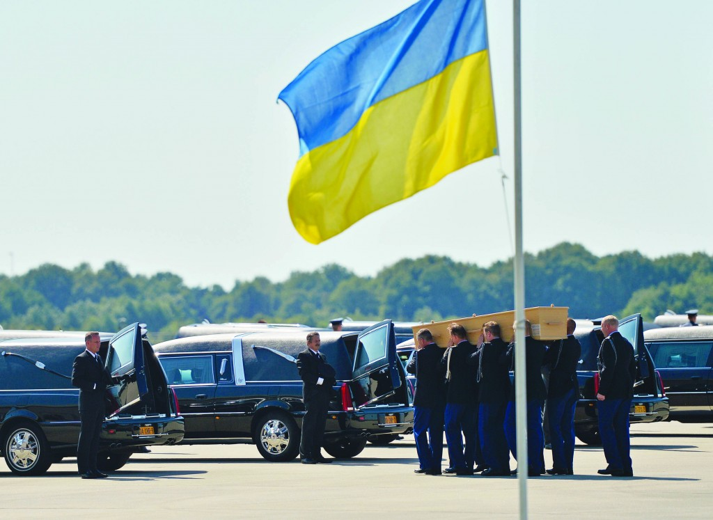 Soldiers load coffins into cars under a Ukrainian flag during a ceremony to mark the return of the first bodies, of passengers and crew killed in the downing of Malaysia Airlines Flight 17, from Ukraine at Eindhoven military air base, Wednesday. (AP Photo/Martin Meissner)