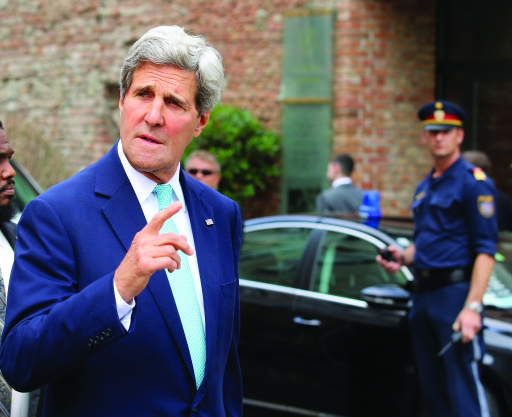 Secretary of State John Kerry gestures as he arrives in front of a hotel where closed-door nuclear talks on Iran take place in Vienna, Austria, Sunday. (AP Photo/Ronald Zak)
