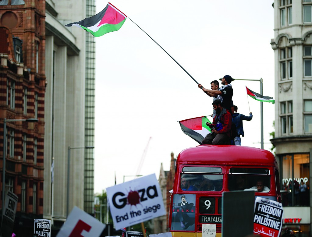 Demonstrators stand and wave flags on top of a No. 9 London Bus during a protest against the air strikes on Gaza, near the Israeli embassy, on Friday.  (AP Photo/Alastair Grant)