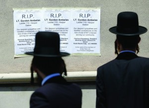 Signs from Williamsburg Jewish community groups on Sunday hang across the street from Ambelas' firehouse. (AP Photo/Seth Wenig)