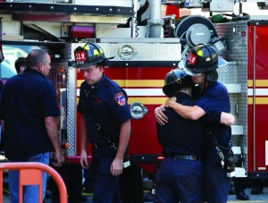Firefighters comfort each other at the firehouse. (AP Photo/Seth Wenig)