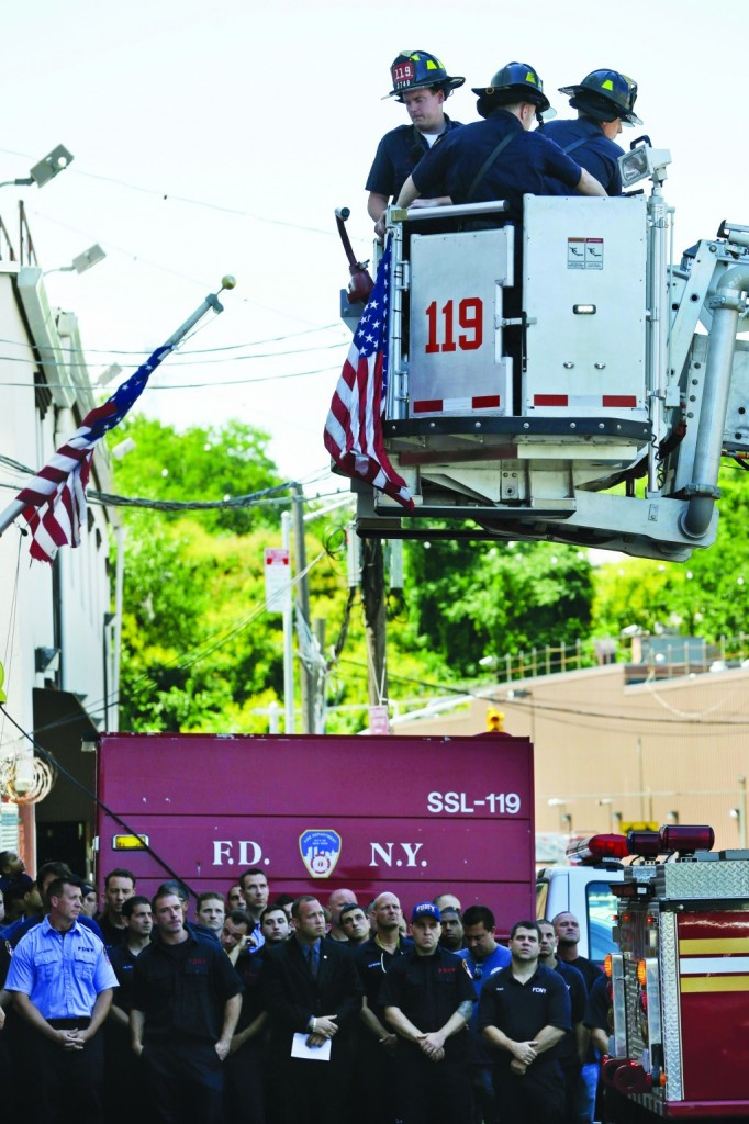 Firefighters on the ground watch Sunday as other firefighters hang bunting in honor of Lt. Gordon Ambelas in Williamsburg. (AP Photo/Seth Wenig)