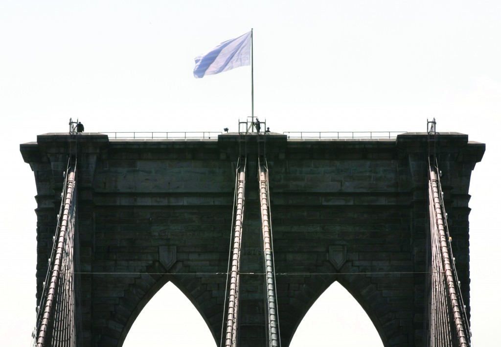 A white surrender flag on Tuesday flutters atop the iconic Brooklyn Bridge, replaced sometime overnight. (AP Photo/Richard Drew)