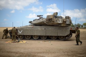 Israeli soldiers working on a Merkava tank, at an army deployment area near Israel's border with the Gaza Strip, on Thursday.(Gili Yaari/Flash90)