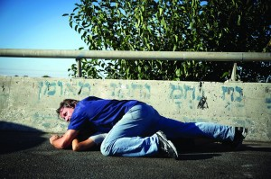An Israeli man seen covering his young son to keep him safe after pulling over on the Yerushalayim-Tel Aviv Highway 1, during a Code Red siren warning of incoming rockets, on Thursday. (Hadas Parush/Flash90)
