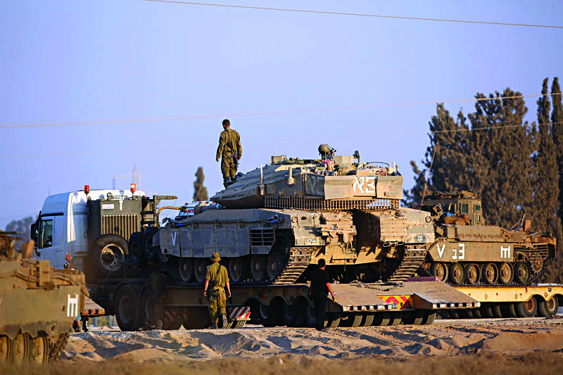 An Israeli Merkava tank takes position at the border with the Gaza Strip, visible in the background, on Monday. (EPA/ABIR SULTAN)