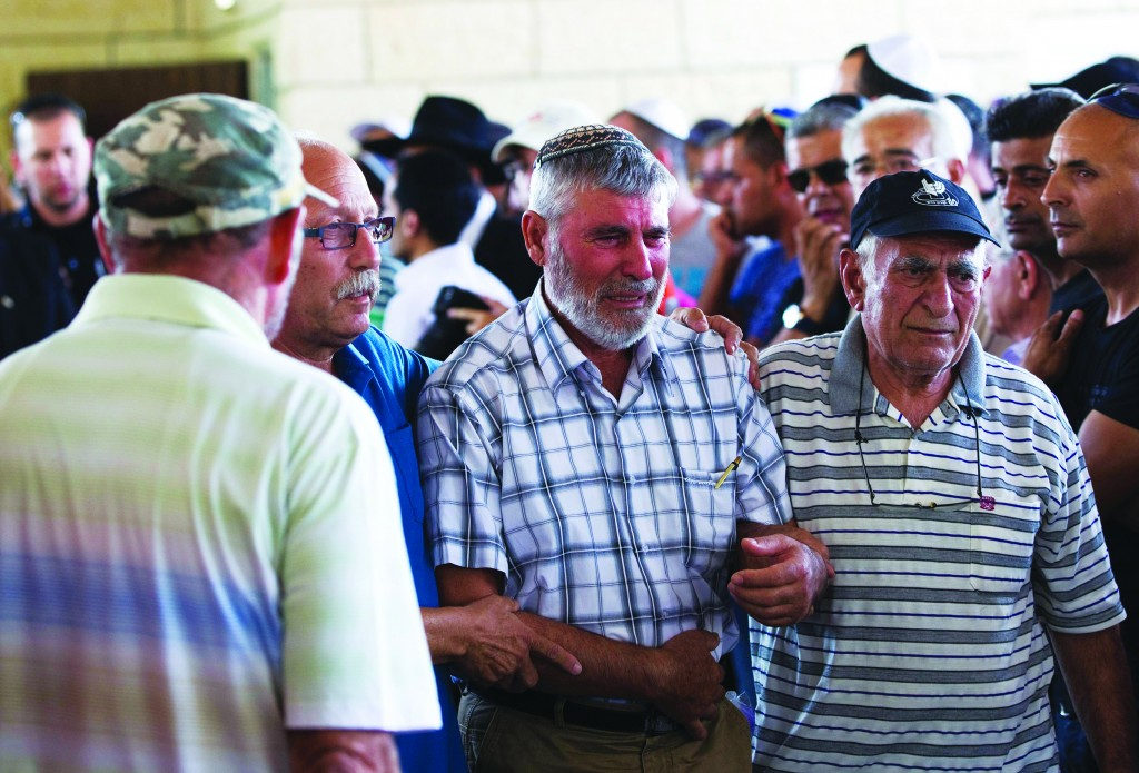 The father (C) of Dror Chanin mourns during his son's levayah in Yehud, east of Tel Aviv, after he was killed on Tuesday by a rocket from Gaza. (REUTERS/Ronen Zvulun)