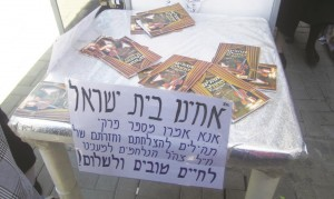 At the busy Bar Ilan Intersection bus stop in Yerushalayim, someone set up a folding table with Tehillim Hamechulak booklets with a note asking people waiting for the bus to use the time to recite Tehillim for soldiers fighting in the South.