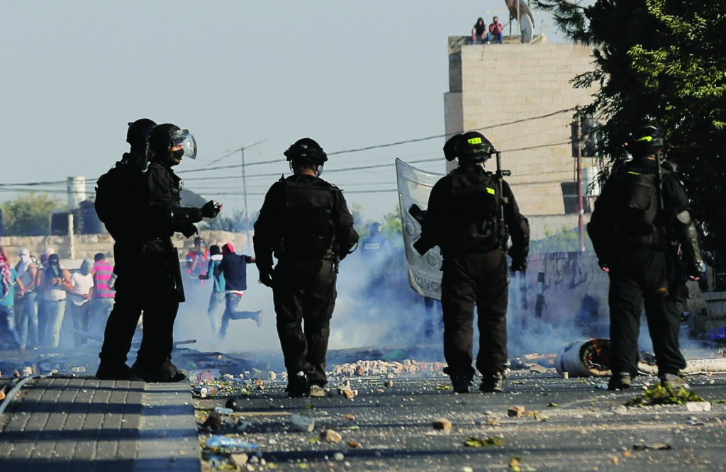 Israeli police look on during clashes with Palestinians in Shuafat, an Arab suburb of Yerushalayim. (REUTERS/Ammar Awad)