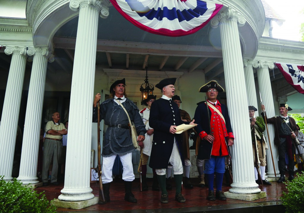 Re-enactor Larry Stephan reads the Declaration of Independence on the porch of Ringwood Manor on Friday, July 4, in Ringwood, N.J. (AP Photo/Northjersey.com, Chris Pedota)