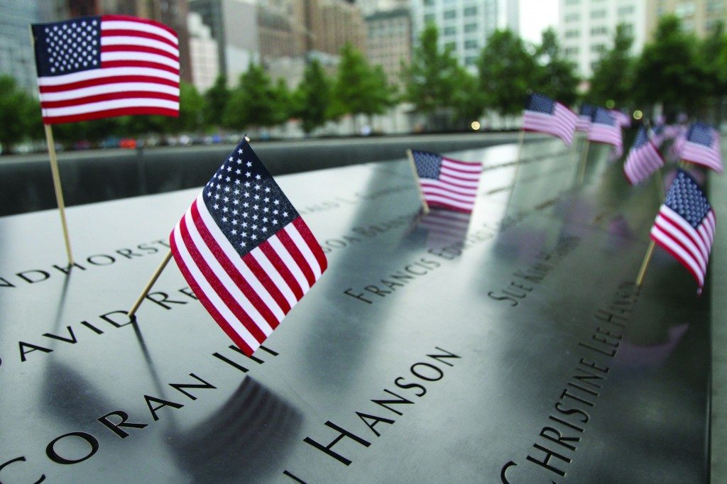 American flags on Friday stand by names at the 9/11 Memorial in Manhattan. A group of severely injured servicemen who served in Afghanistan and/or Iraq participated in the event. (AP Photo/Tina Fineberg)