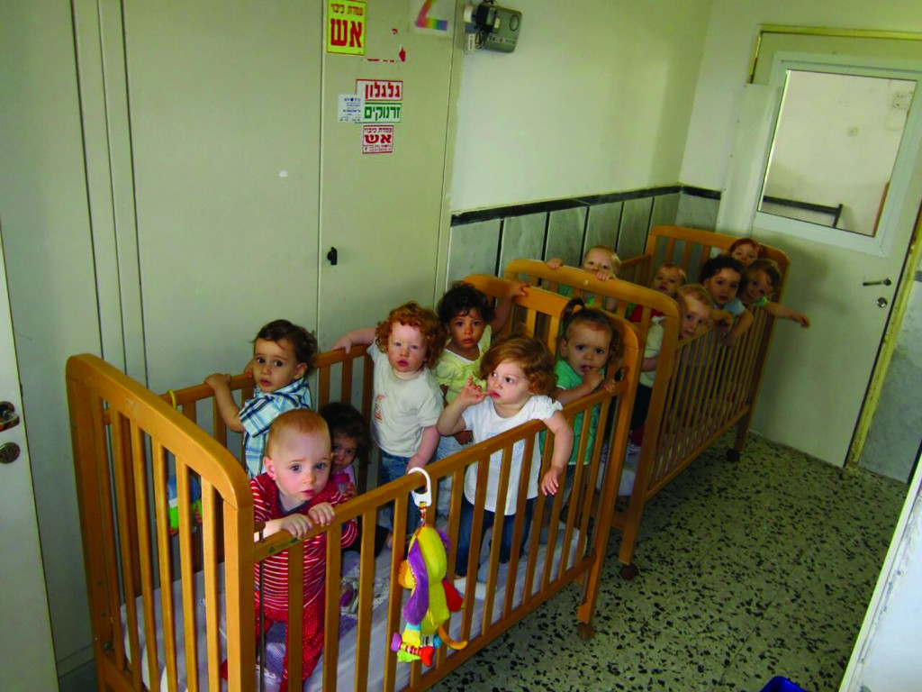 As the sirens sound in Bnei Brak, children are brought to shelter in day care center hallway.