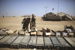 Israeli soldiers search boxes they received from Israeli citizens for something to eat after they readied their gear in a staging area at an undisclosed location close to the Gaza Strip border, in southern Israel on Monday. (EPA/ABIR SULTAN)