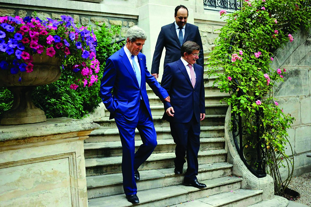 U.S. Secretary of State John Kerry (L), Qatari Foreign Minister Khaled al-Attiyah (back) and Turkish Foreign Minister Ahmet Davutoglu walk down a staircase as they continue discussions regarding a cease-fire between Hamas and Israel in Gaza, at the Turkish ambassador's residence in Paris. (REUTERS/Charles Dharapak/Pool)
