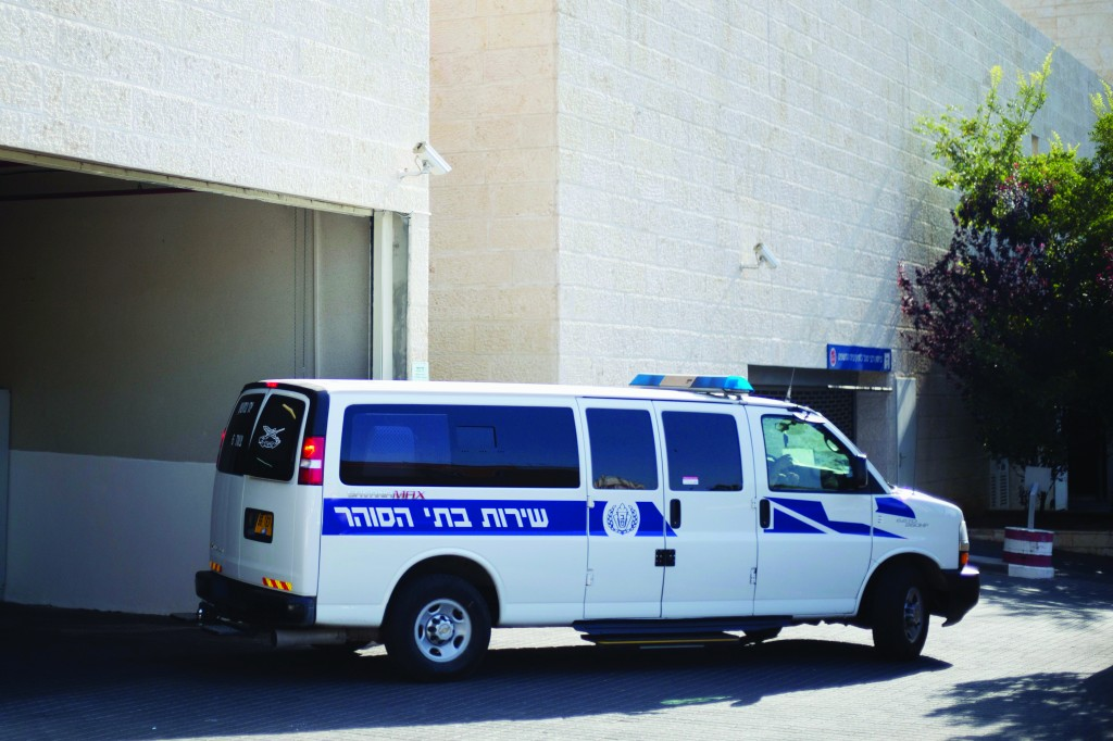 An Israeli prison service vehicle leaves the court house in Petach Tikva, Sunday.  Top inset: Israeli court security officers stand guard at the entrance to a courtroom in Petach Tikva, Israel, Sunday. (AP Photo/Ariel Schalit)