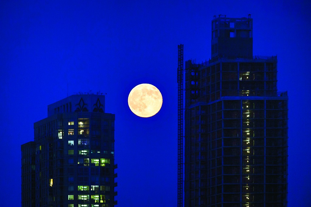 "An unusually large ""supermoon"" rises over Queens on Saturday, a phenomenon caused by a seasonal closeness to Earth. Two other supermoons will come this summer, on Aug. 10 and Sept. 9. (AP Photo/John Minchillo)"