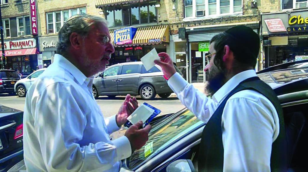 Assemblyman Dov Hikind gives a Boro Park driver  a muni-meter receipt holder.