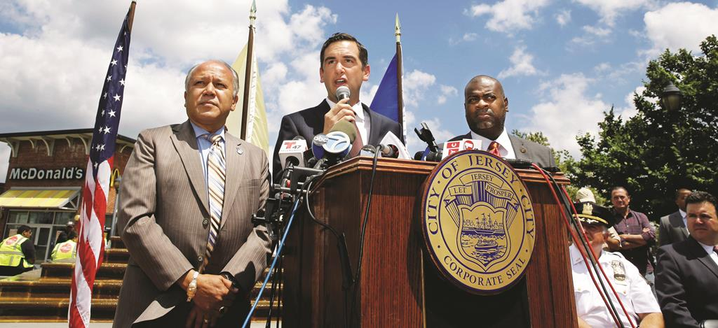 Mayors of Paterson (L) and Newark (R) listen Monday as Jersey City Mayor Steven Fulop answers a question after New Jersey's three largest cities announced that they are looking at ways to pool resources to tackle violent crime. (AP Photo/Mel Evans)