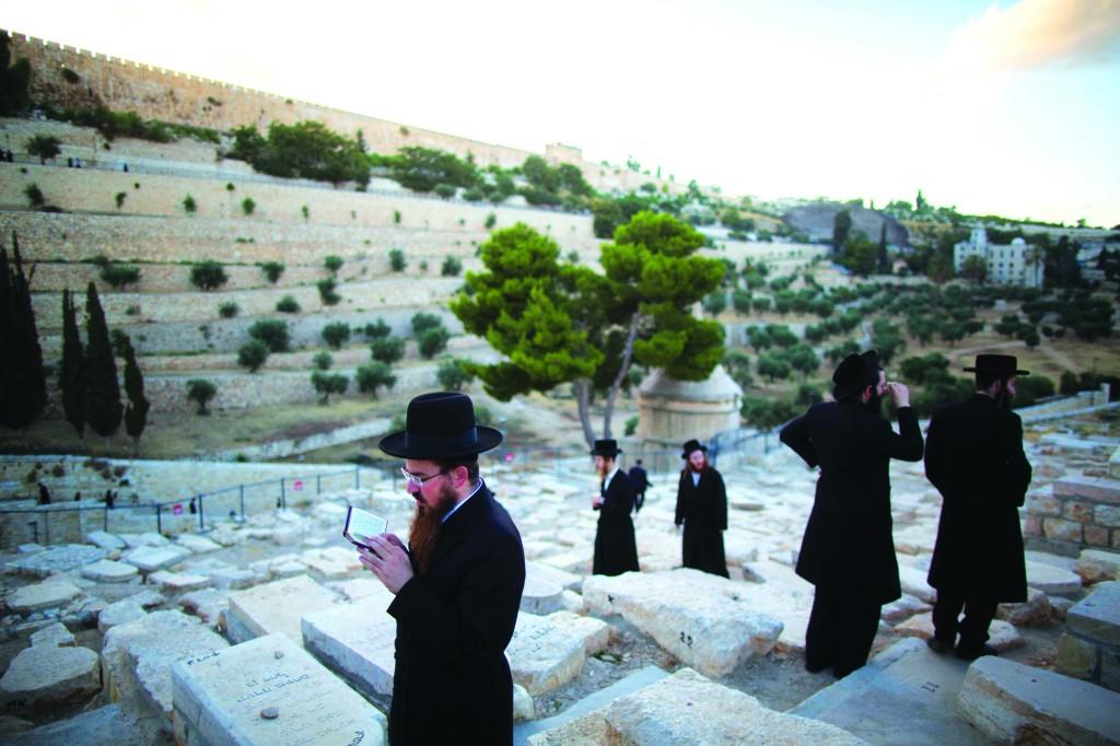 Men daven at the kever of the Ohr Hachaim on Har Hazeisim, Sunday, July 13.  (Yonatan Sindel/Flash90 )