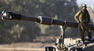 An Israeli soldier leans on the barrel of the gun of a mobile artillery unit at a position on the Israel-Gaza border, during Operation Protective Edge.  (AP Photo/Lefteris Pitarakis)