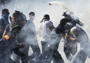 Violent pro-Palestinian protestors react to tear gas during clashes with riot police officers following a protest at Place de la Republique in Paris, France, Saturday (EPA/ETIENNE LAURENT)