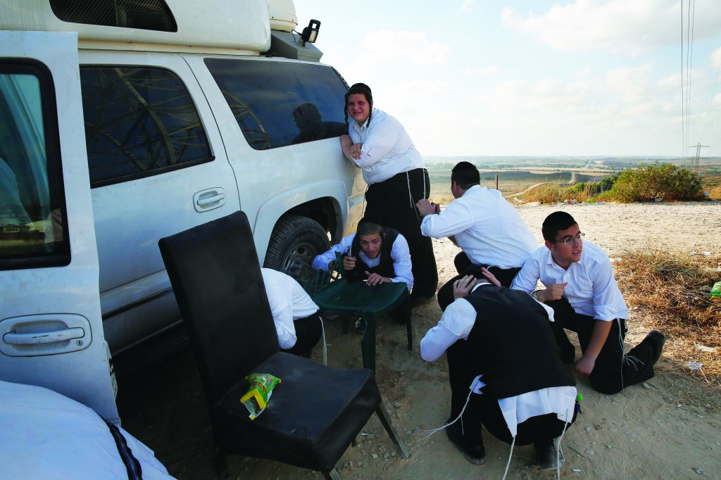 Israelis take cover as a rocket is fired from the Gaza Strip while visiting a hilltop overlooking the Gaza Strip near the southern town of Sderot July 15, 2014.  (REUTERS/Baz Ratner)