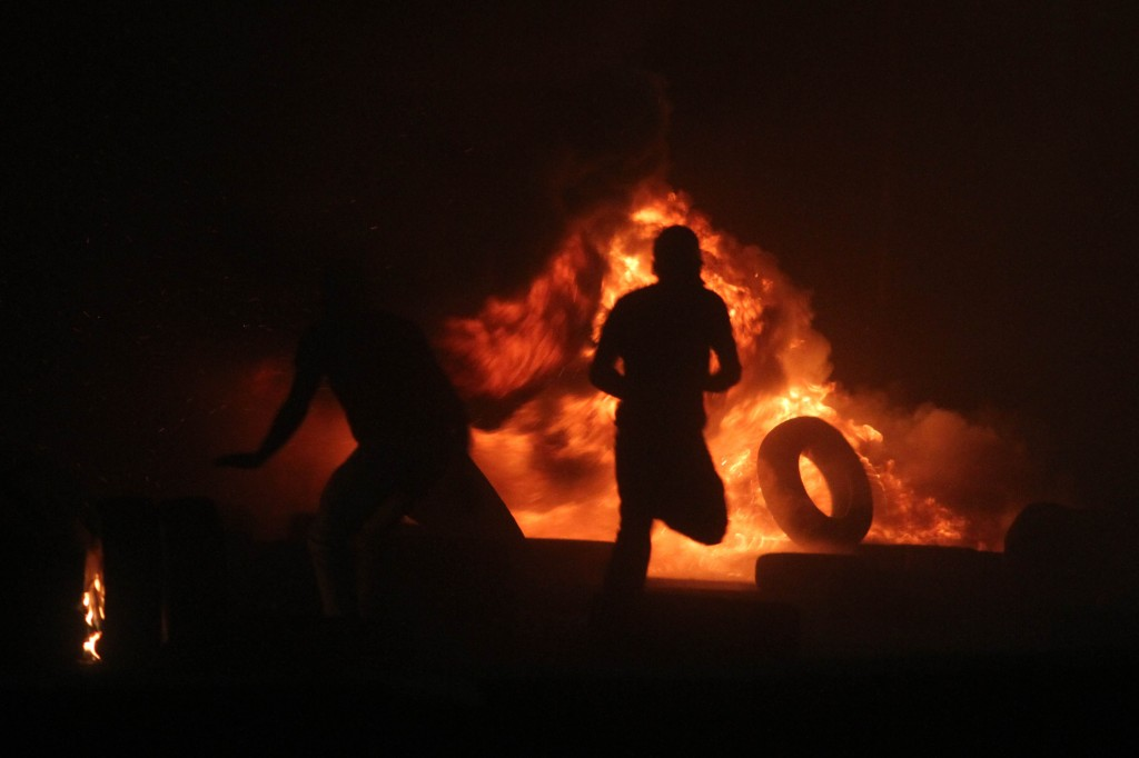 Palestinian men burn tires during a violent protest at the Qalandiya checkpoint. (Issam Rimawi/FLASH90)