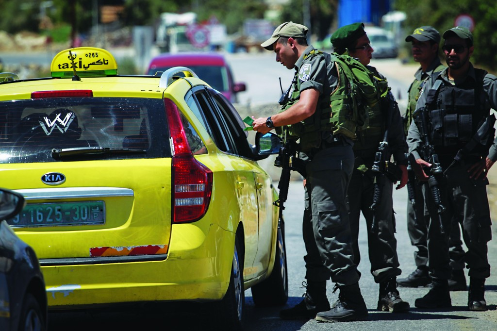 Israeli security forces checking Palestinians at the entrance to Halhul, near Chevron on Tuesday.  (Hadas Parush/Flash90)
