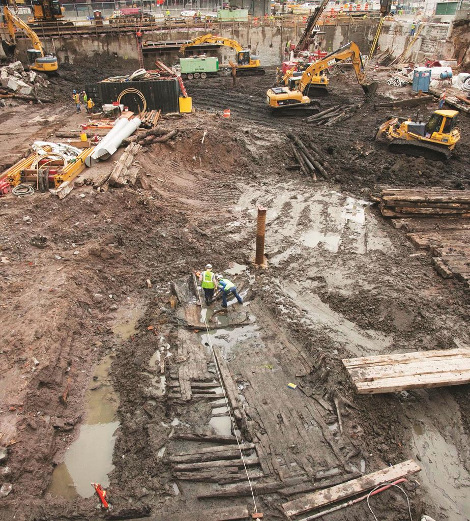 Archaeologists measure the wood hull of a ship unearthed at the World Trade Center site and dated to 1773. (AP Photo/Mark Lennihan)