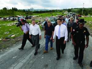 Gov. Andrew Cuomo, second from right, on Wednesday walks with local elected and law enforcement officials as they survey the damage from Tuesday night's storm in Smithfield, N.Y. (AP Photo/Mike Groll)