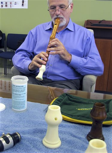 In this July 17, 2014 photo, Dr. Robert Howe, a medical doctor and a PhD candidate in music history, plays an antique recorder that was repaired using a 3-D printing of the instrument's original bell, at the University of Connecticut's Depot Campus in Mansfield, Conn. Howe and his colleagues have been using CT scans and 3-D printing to unlock the secrets of antique instruments and make replica parts that will allow them to be played. (AP Photo/Pat Eaton-Robb)