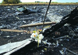 A toy bear on the charred plane fuselage parts, as people walk through the crash site. (AP Photo/Vadim Ghirda)