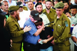 "Uri Greenberg (2nd R), son of killed Israeli soldier Amotz Greenberg, Hy""d, is embraced by his grandfather during the levayah in the Hod Hasharon cemetery, July 20.  (EPA/ABIR SULTAN)"