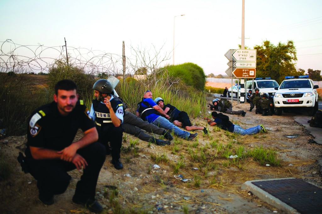 Israeli police officers take cover during an infiltration by Hamas terrorists near Kibbutz Zikim.  IDF units killed four Hamas terrorists in a shootout as they attempted to infiltrate Israel from the sea at Zikim beach on Tuesday. One soldier was lightly wounded in the exchange of gunfire. A senior security official said an IDF force was dispatched to Zikim beach after the military detected suspicious movements in the area. (REUTERS/Amir Cohen )