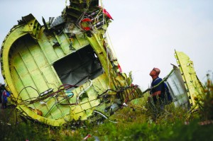 A Malaysian air crash investigator inspects the crash site of Malaysia Airlines Flight MH17.. (REUTERS/Maxim Zmeyev )