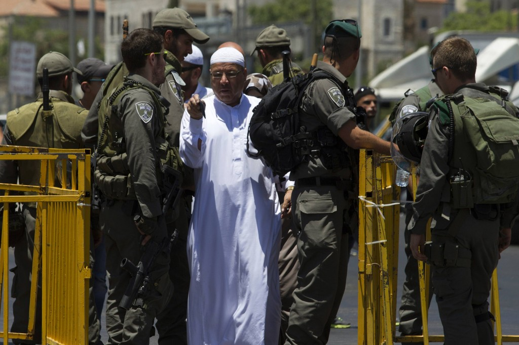 A man walks past a checkpoint manned by Israeli police after showing his identity card. (REUTERS/Siegfried Modola)