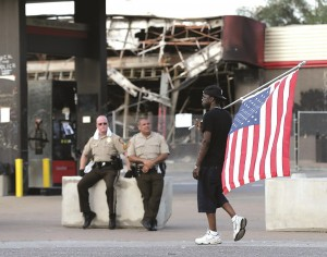 Duane Merrells walks past a burned-out gas station with an upside-down flag during a protest Monday in Ferguson, Missouri. (AP Photo/Charlie Riedel)