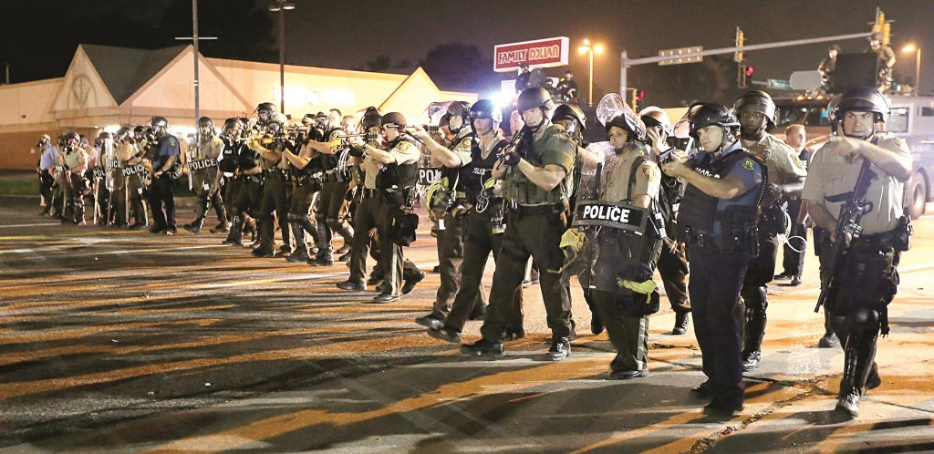 Police advance to clear people during a protest on behalf of Michael Brown in Ferguson, Missouri.. (AP Photo/Charlie Riedel)