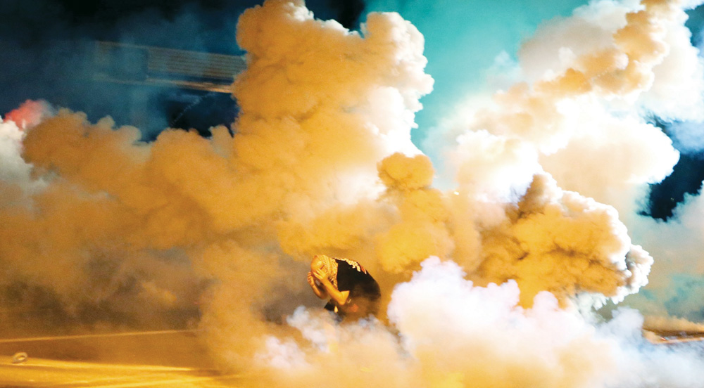 A protester takes shelter from smoke billowing around him Wednesday, in Ferguson, Mo. (AP Photo/St. Louis Post-Dispatch, David Carson)