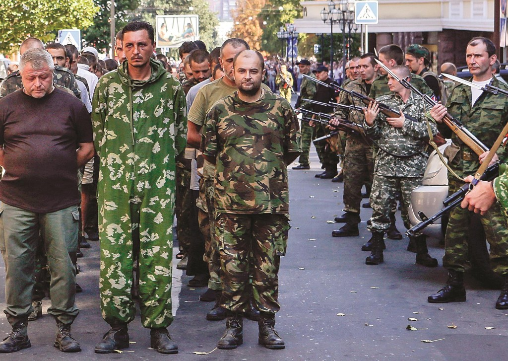 Armed pro-Russian separatists (R) escort a column of Ukrainian prisoners of war as they walk across central Donetsk on Sunday. (REUTERS/Maxim Shemetov)