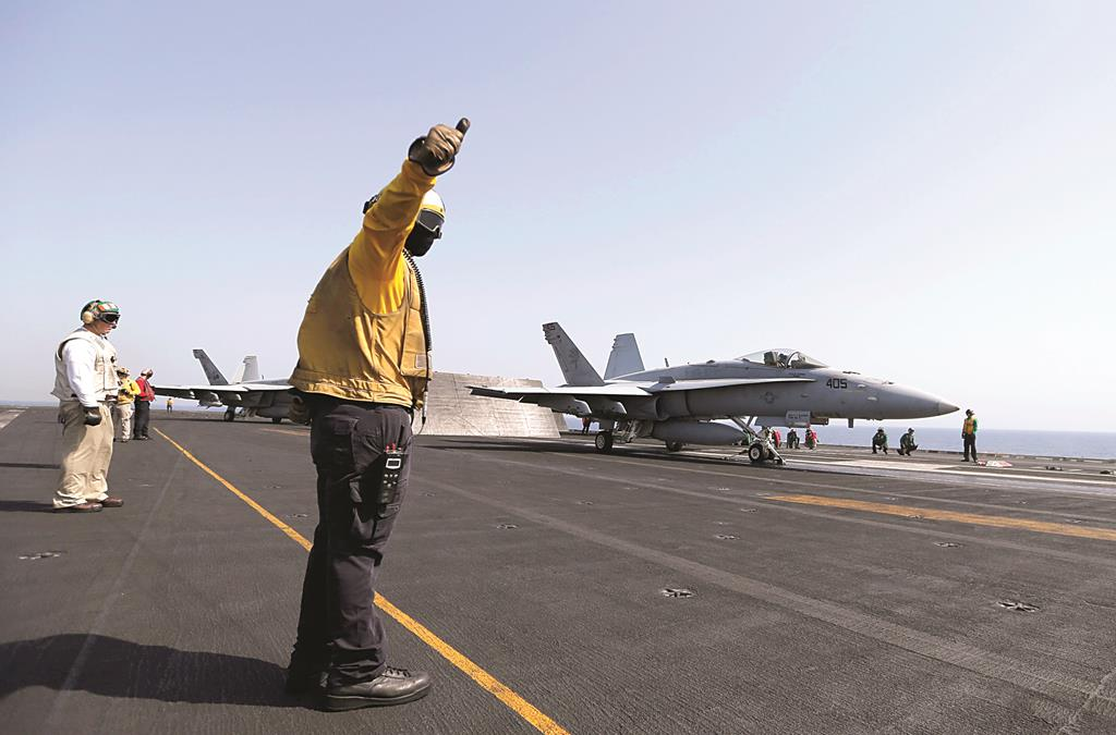 Flight deck crew member gives a thumbs up to take off to pilot of F/A-18C Hornet of Strike Fighter Squadron to take off the aircraft carrier USS George H.W. Bush, in the Gulf Tuesday, 2014. Planes have been taking off from the USS George H.W. Bush to strike key positions taken over by the Islamic State fighters in Iraq.  (REUTERS/Hamad I Mohammed)