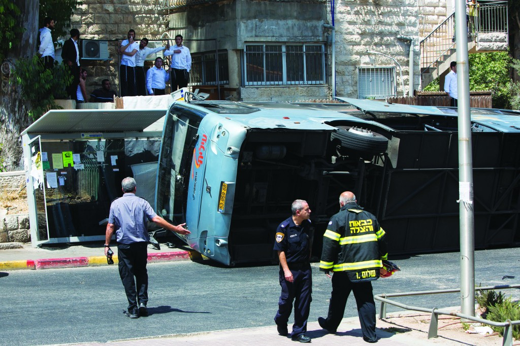 """Security personnel at the scene in Yerushalayim, Monday, where an Arab from the neighborhood of Jabel Mukaber used a tractor to overturn a bus on Shmuel HaNavi Street. The Arab first drove into a pedestrian, who died of his wounds, Hy""""d. Then he used the tractor to flip the bus, injuring the driver and three people. (Yonatan Sindel/Flash90)"""