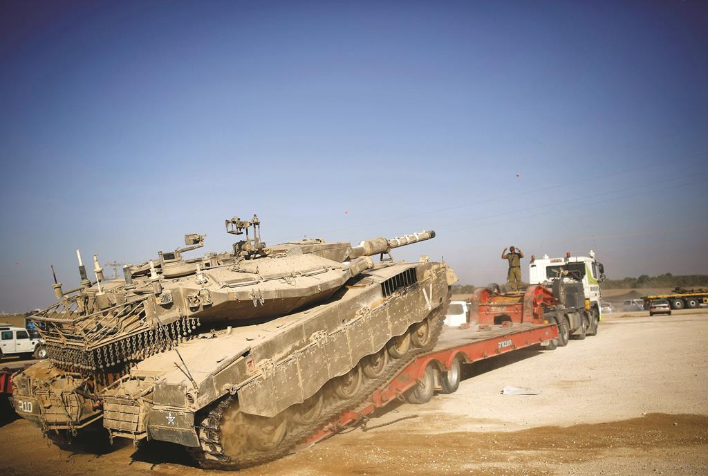 An Israeli soldier directs a tank onto a truck for transport near the border with Gaza, Wednesday. (REUTERS/Amir Cohen)