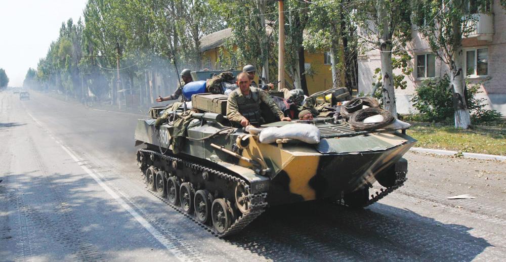 Ukrainian servicemen ride on an armoured vehicle during a patrol in the eastern Ukrainian town of Vuhlehirsk Thursday. (REUTERS/Valentyn Ogirenko)