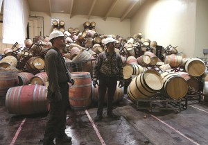 Workers survey a mound of toppled wine barrels that sit in a storage room at Kieu Hoang Winery in Napa, California.  (Justin Sullivan/Getty Images)